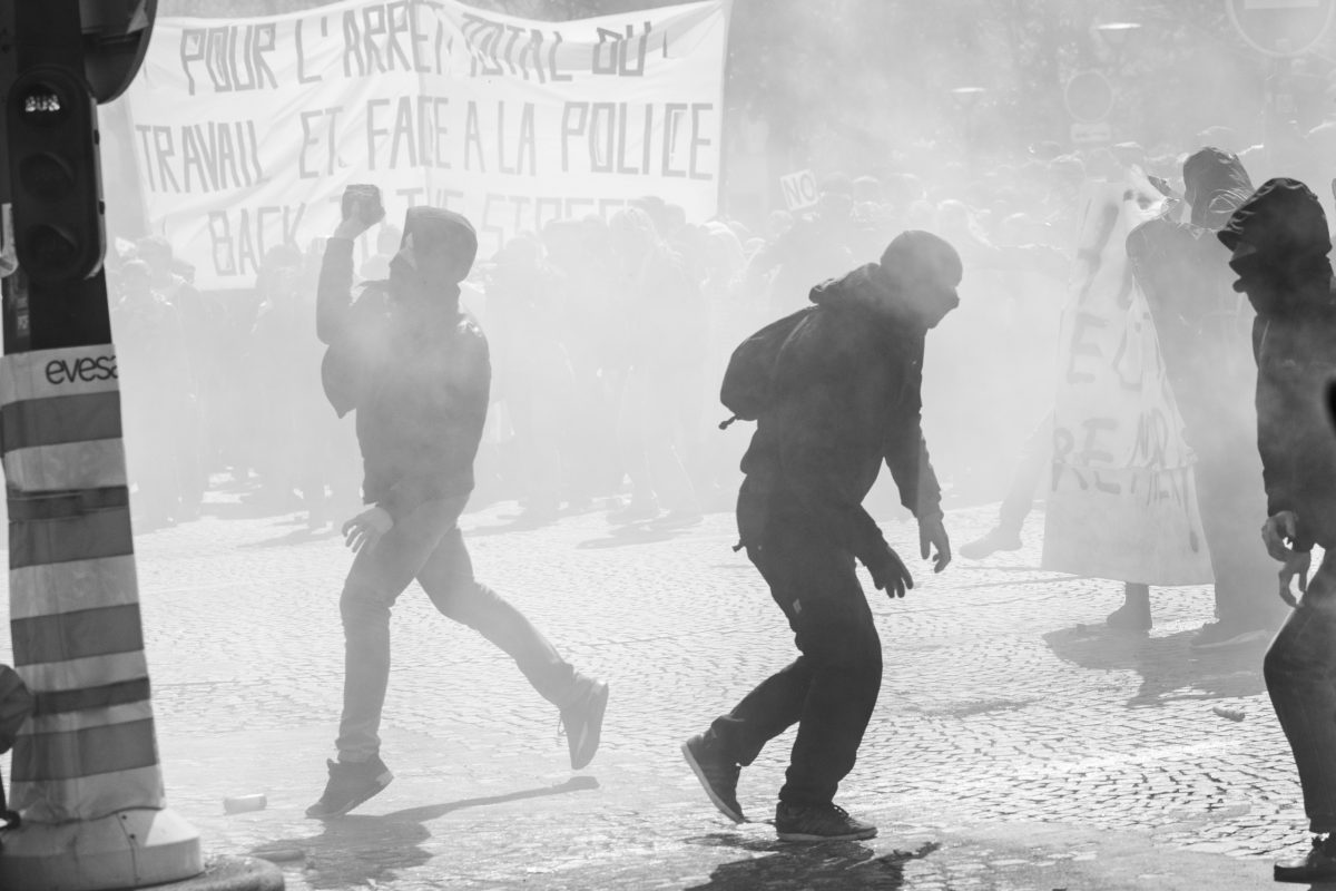 Protester throwing a stone surrounded by tear gas | © Christian Martischius