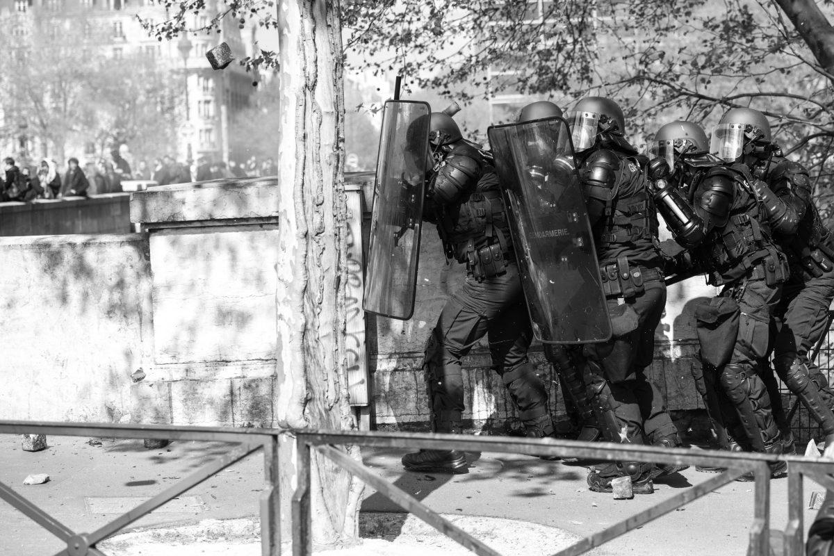 Riot police hiding behind their shields to fend of a stone | © Christian Martischius