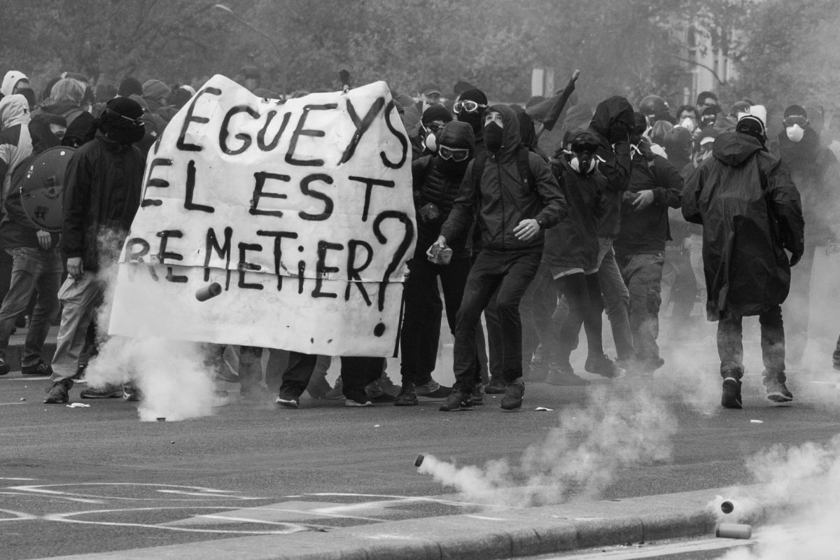 Protesters holding a banner surrounded by tear gas grenades | © Christian Martischius
