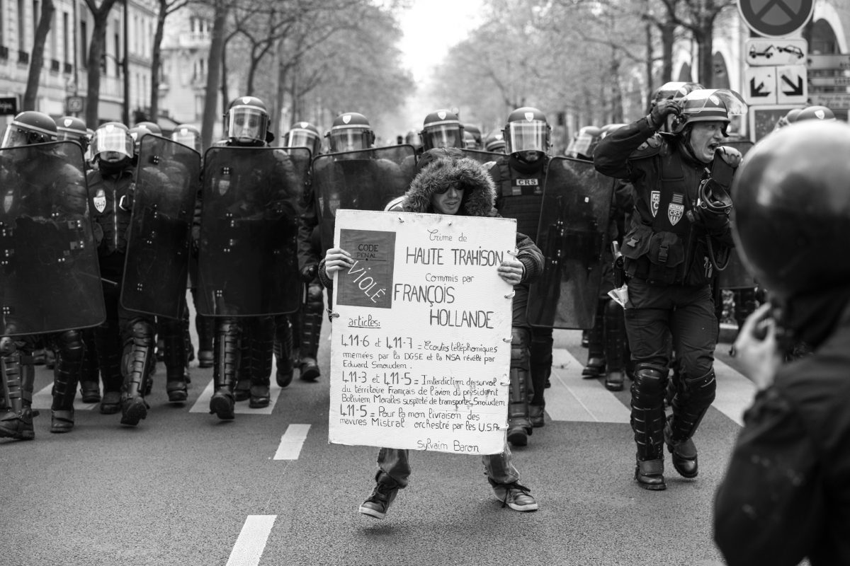 Protester with sign in front of approaching riot police | © Christian Martischius