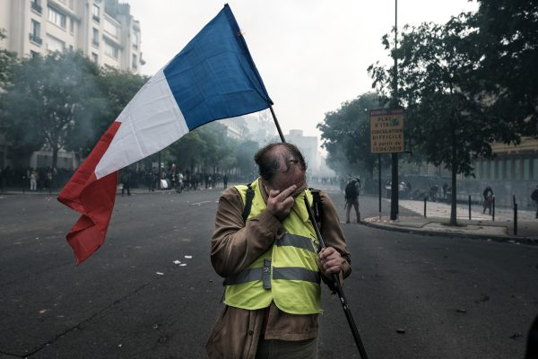 A member of the yellow vests movement covering his eyes due to the tear gas which covered whole streets of houses